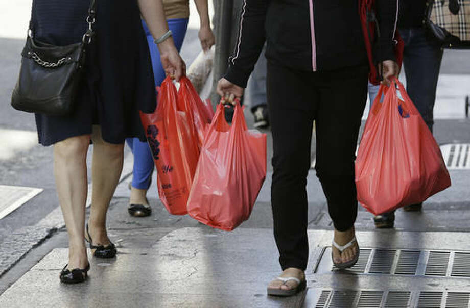 FILE - In this Sept. 20, 2016, file photo, women walk with plastic bags through Chinatown in San Francisco. California voters have narrowly approved a statewide ban on single-use plastic carryout bags. Proposition 67 was placed on the November 8, 2016, ballot by plastic bag industry supporters to try to overturn a ban approved by the state legislature two years ago. (AP Photo/Eric Risberg, File) Photo: Eric Risberg