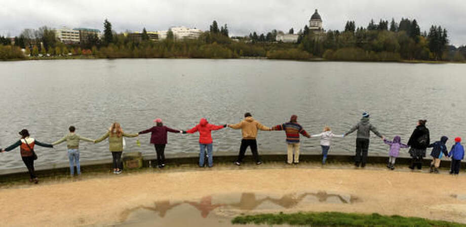 A section of an estimated group of well-over one thousand join hands along Capitol Lake in Olympia, Wash., Wednesday, Nov. 23, 2016, while taking part in the Hands Around Capitol Lake event. According to its organizers the goal of the gathering is to help promote the idea of peace in the wake of what many feel was a decisive political season. (Steve Bloom/The Olympian via AP) Photo: Steve Bloom