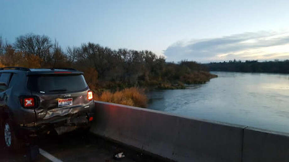 In this photo provided by Oregon State Police, a damaged car is shown on an Interstate 84 bridge over the Snake River on the Idaho/Oregon border near Ontario, Ore., Monday, Nov. 21, 2016. An Idaho man not only survived being hit by a car on an icy interstate highway bridge but also a 50-foot-fall into a river and a swim through its frigid waters with a badly broken leg, authorities said. (Oregon State Police via AP) Photo: Uncredited
