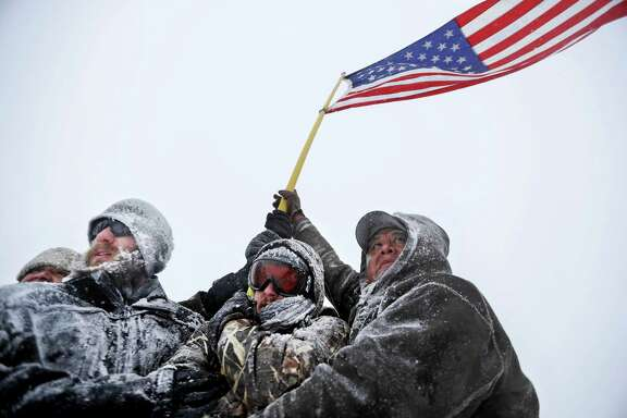Military veterans huddle together in the face of strong winds during a march against the Dakota Access pipeline in North Dakota.
