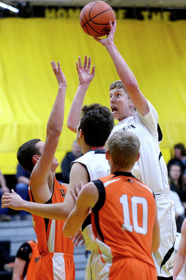 NICK KING | nking@mdn.net  Bullock Creek's Scott Spica, right, shoots over Merrill's Jake Knierim, left, during the first quarter on Monday at Bullock Creek High School. / Midland Daily News