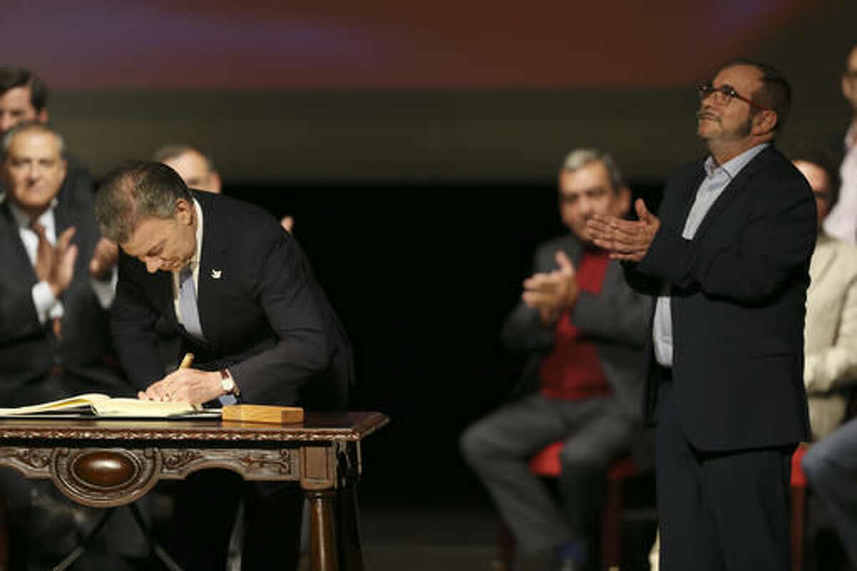 Colombia's President Juan Manuel Santos signs a modified peace accord with rebels of the Revolutionary Armed Forces of Colombia, FARC, as rebel top leader Rodrigo Londono, known and Timochencko, right, applauds at Colon Theater in Bogota, Colombia, Thursday, Nov. 24, 2016. The original accord ending the half century conflict was rejected by voters in a referendum last month. (AP Photo/Fernando Vergara)