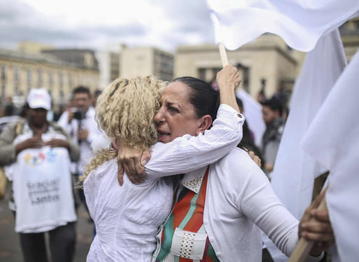 Women hug during a rally in support of the peace process with rebels of the Revolutionary Armed Forces of Colombia, FARC, a few blocks from the venue where Colombia's President Juan Manuel Santos and top FARC rebel leader Rodrigo Londono are signing a revised peace pact, at the main square in downtown Bogota, Colombia, Thursday, Nov. 24, 2016. An original accord ending the half century conflict was rejected by voters in a referendum last month. (AP Photo/Ivan Valencia)