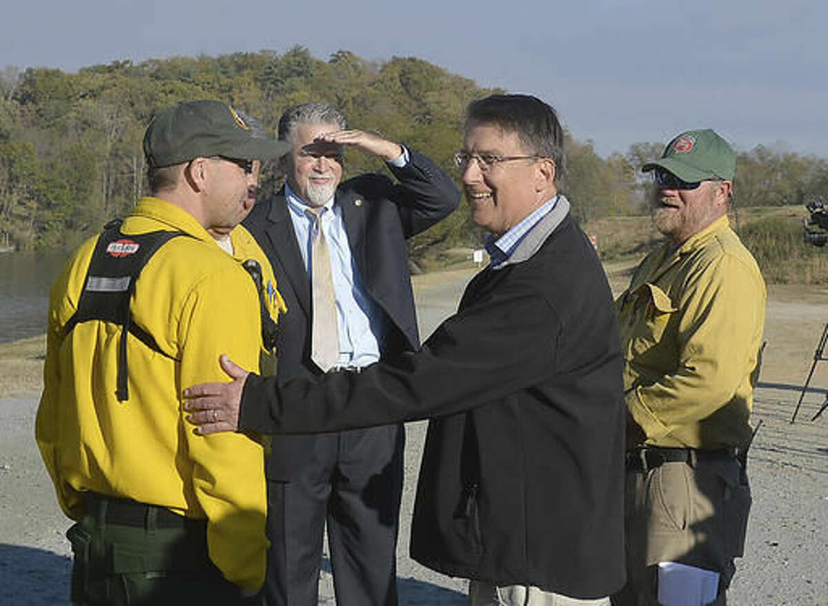 North Carolina Gov. Pat McCrory, second right, thanks fire crews as he tours the command center near the Party Rock Fire at Lake Lure, N.C., Thursday afternoon, Nov. 10, 2016. A state of emergency is in effect for 25 western North Carolina counties where active wildfires are burning, caused by the drought that began last spring. Gov. Pat McCrory said in a news release Thursday that he was declaring the state of emergency for one-quarter of North Carolina's 100 counties. (Patrick Sullivan/The Times-News via AP)