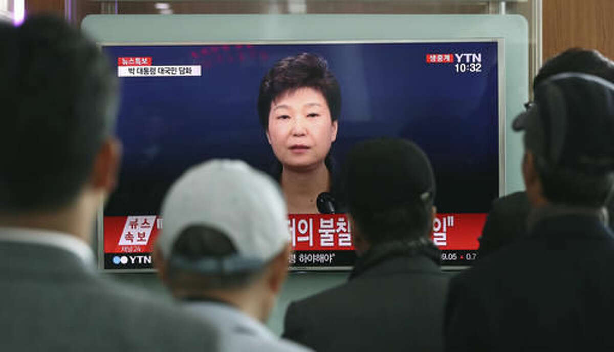 """FILE - In this Friday, Nov. 4, 2016 file photo, people watch a TV screen showing the live broadcast of South Korean President Park Geun-hye's address to the nation on a """"heartbreaking"""" scandal, at the Seoul Railway Station in Seoul. South Korean prosecutors are likely to question Park over suspicion that she let a shadowy longtime confidante manipulate power from behind the scenes, state-run Yonhap news agency reported Sunday, Nov. 13. (AP Photo/Lee Jin-man, File)"""