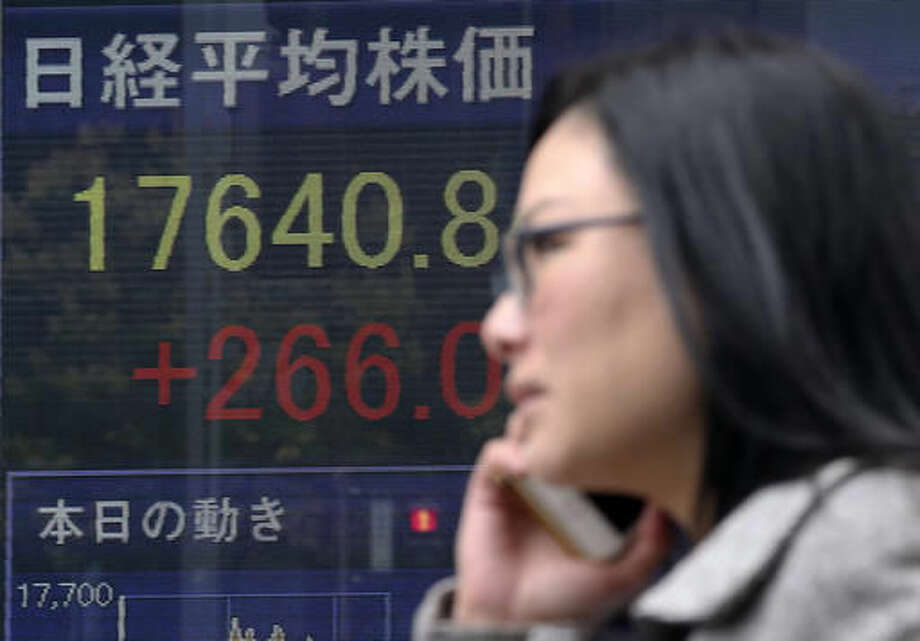 A woman walks by an electronic stock board of a securities firm in Tokyo, Monday, Nov. 14, 2016. Asian shares were mostly lower Monday but Japan's benchmark got a boost from a weaker yen. Other regional bourses have gradually steadied after a bout of turmoil following the U.S. presidential election. (AP Photo/Koji Sasahara) Photo: Koji Sasahara