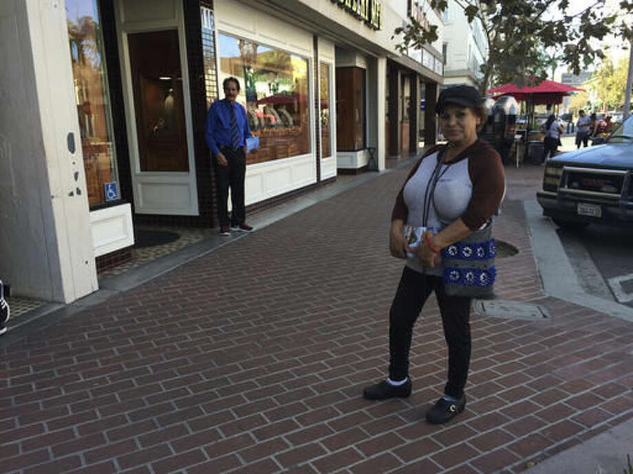 Alicia Ramirez, 67, hands out fliers to passers-by on a busy street in a largely Latino area lined with money transfer businesses and shops selling elegant gowns for quinceanera celebrations, on Wednesday, Nov. 9, 2016, in Santa Ana, Calif. She said she's afraid of what a Trump victory will mean for immigrants like her who lack legal papers. (AP Photo/Amy Taxin) Photo: Amy Taxin