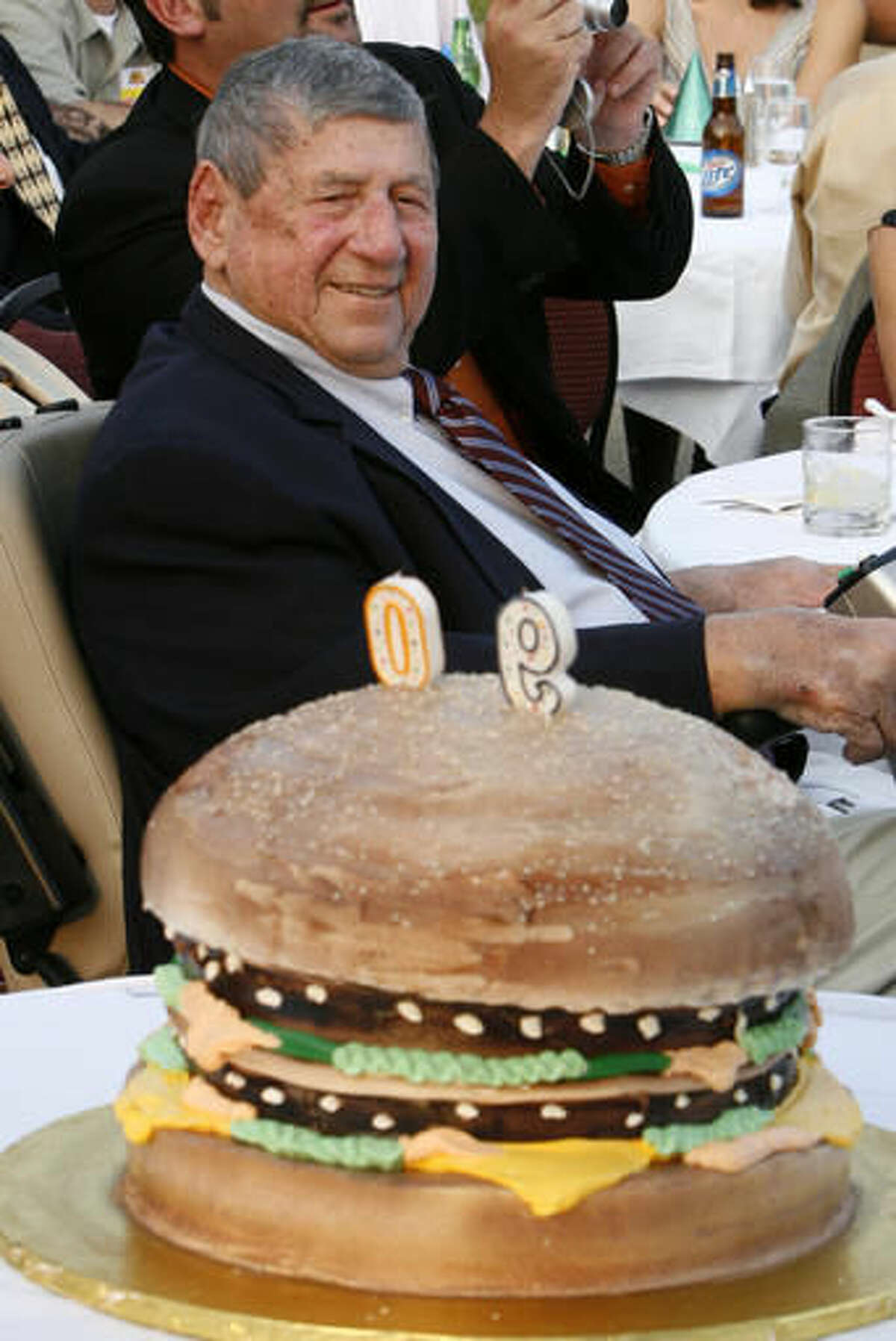 """FILE - In this Aug. 21, 2008, file photo, Big Mac creator Michael """"Jim"""" Delligatti sits behind a Big Mac birthday cake at his 90th birthday party in Canonsburg, Pa. Delligatti, the Pittsburgh-area McDonald's franchisee who created the Big Mac in 1967, has died. He was 98. (AP Photo/Gene J. Puskar, File)"""