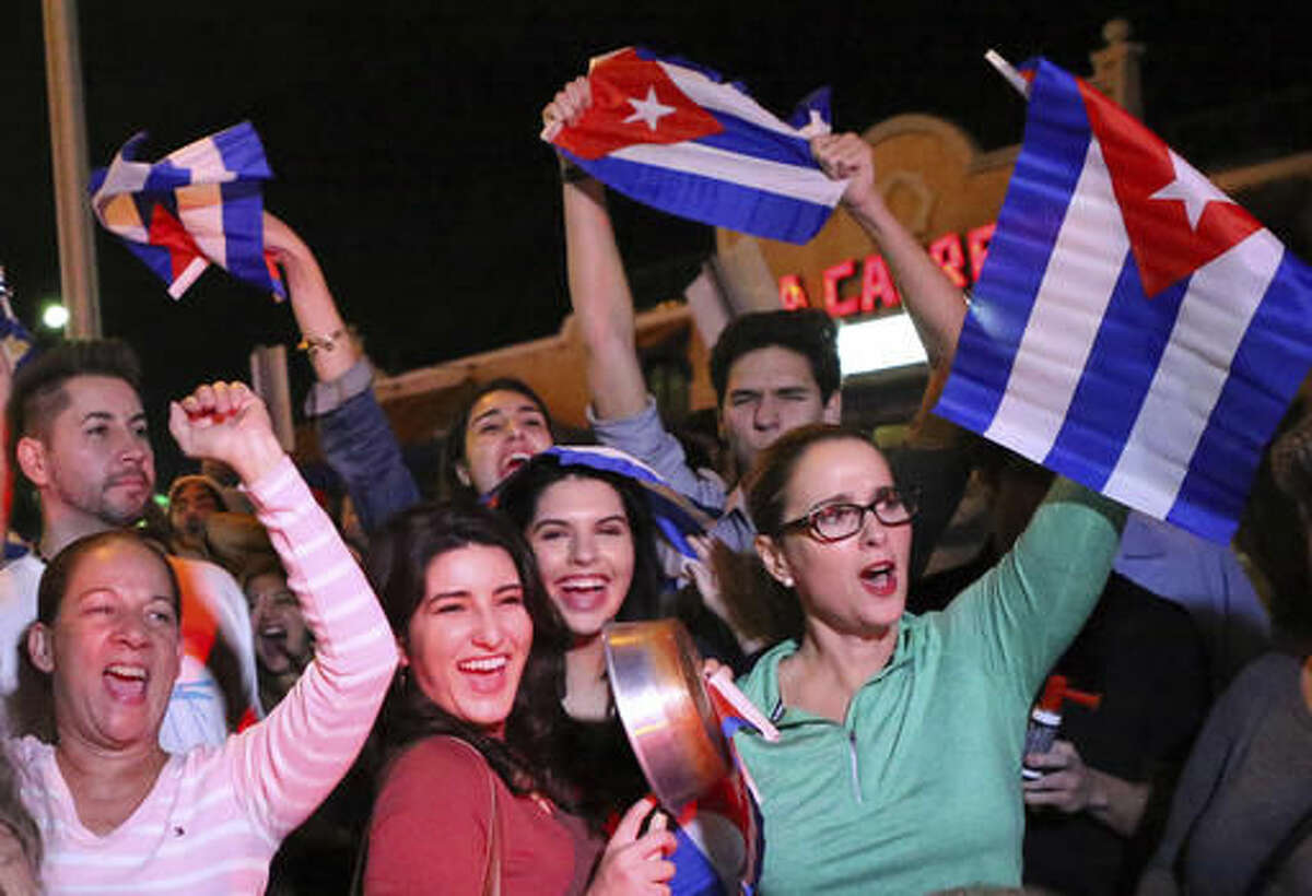 FILE- In this Nov. 25, 2016, file photo, the Cuban community in Miami celebrates the announcement that Fidel Castro died in front La Carreta Restaurant early in Miami. For the hundreds of thousands of children born of Cuban exiles, some who are two and three generations removed from the island, Fidel Castro's death potentially opens a door to a world previously off-limits. (David Santiago/El Nuevo Herald via AP, File)