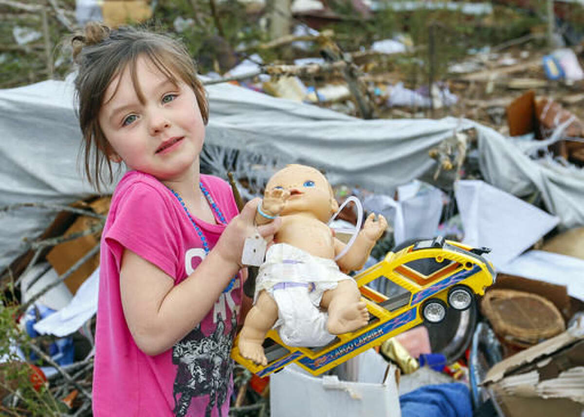 Serenity Brooks, 5, holds a baby doll as she digs for her belongings after a suspected tornado ripped through the town of Rosalie, Ala., Wednesday, Nov. 30, 2016. (AP Photo/Butch Dill)