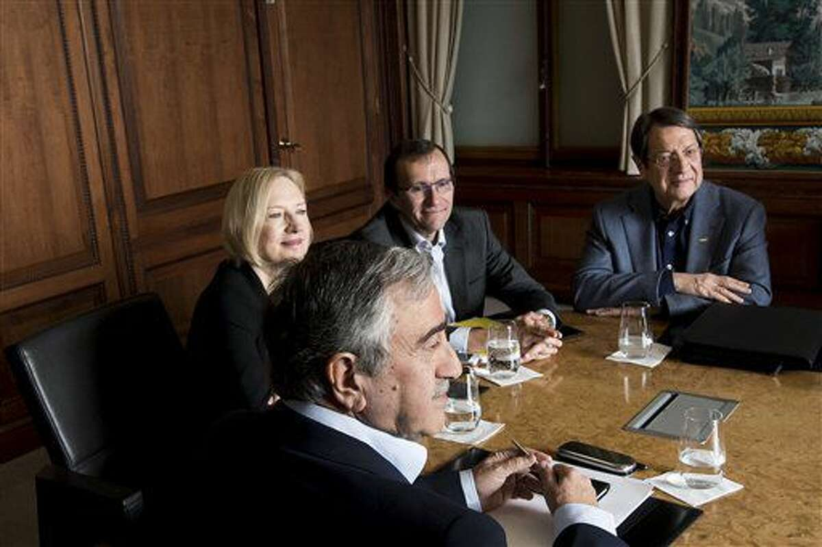 Turkish Cypriot leader Mustafa Akinci, left, speaks with Greek Cypriot President Nicos Anastasiades, right, next to Special Adviser to the United Nations Secretary-General on Cyprus Espen Barth Eide, 2nd right, and Elizabeth Spehar, Deputy to the Secretary-General's Special Adviser on Cyprus, 2nd left, during the Cyprus Talks, in Mont Pelerin, Switzerland Sunday, Nov. 20, 2016. (Jean-Christophe Bott/Keystone via AP)