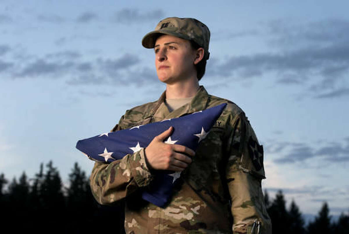 """FILE - In this Aug. 28, 2015 file photo, Capt. Jennifer Peace holds a flag as she stands for a photo near her home in Spanaway, Wash. Peace has been been deployed around the world, including Iraq and Afghanistan. When an officer suggested she leave the military rather than deal with the fallout of being a transgender soldier, Peace was taken aback. """"I couldn't believe he said that. I've been in the military for 11 years. It's everything to me. It's what I do. It's as much a part of me as anything else."""" (Drew Perine/The News Tribune via AP)"""