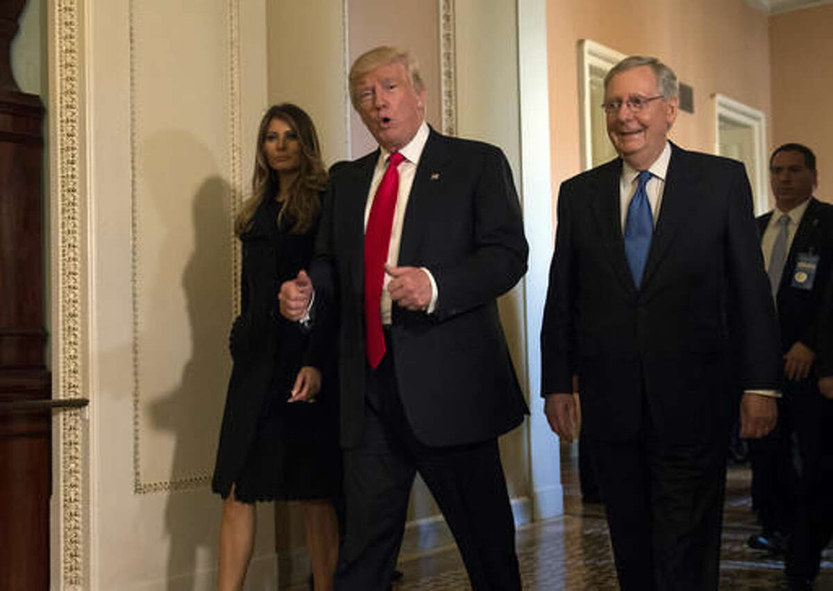 In this Nov. 10, 2016, photo, President-elect Donald Trump, accompanied by his wife Melania, and Senate Majority Leader Mitch McConnell of Ky., gestures while walking on Capitol Hill in Washington. Washington's new power trio consists of a bombastic billionaire, a telegenic policy wonk, and a taciturn political tactician. How well they can get along will help determine what gets done over the next four years, and whether the new president's agenda founders or succeeds. (AP Photo/Molly Riley)