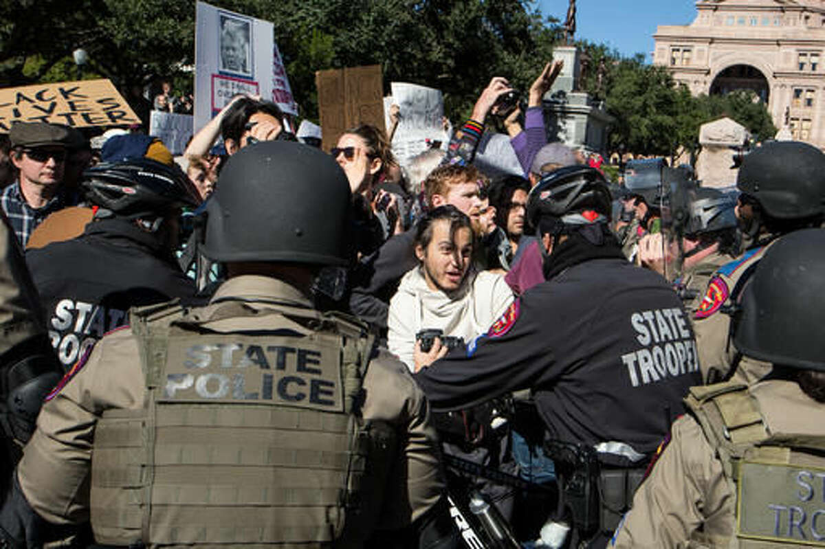 Police use their bicycles to push back counter-protestors to a White Lives Matter rally outside the Texas State Capitol in Austin, Texas, on Saturday, Nov. 19, 2016. Earlier in the day, officials unveiled a monument recognizing the contributions of African-Americans to the state. (Dave Creaney/Austin American-Statesman via AP)