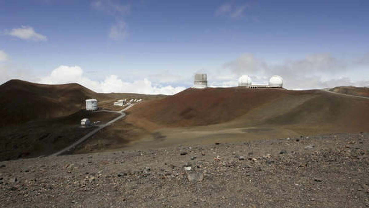 FILE - In this Aug. 31, 2015 file photo, observatories sit atop Hawaii's Mauna Kea, near Hilo, Hawaii. Hearings are still underway for a permit to build what would be one of the world's largest telescopes in Hawaii, but a group challenging the project is already appealing to the state Supreme Court. Thirty Meter Telescope opponents are challenging various decisions that have been made regarding contested-case proceedings, including affirming the hearings officer and an order limiting cross-examination to 30 minutes per party. (AP Photo/Caleb Jones, File)