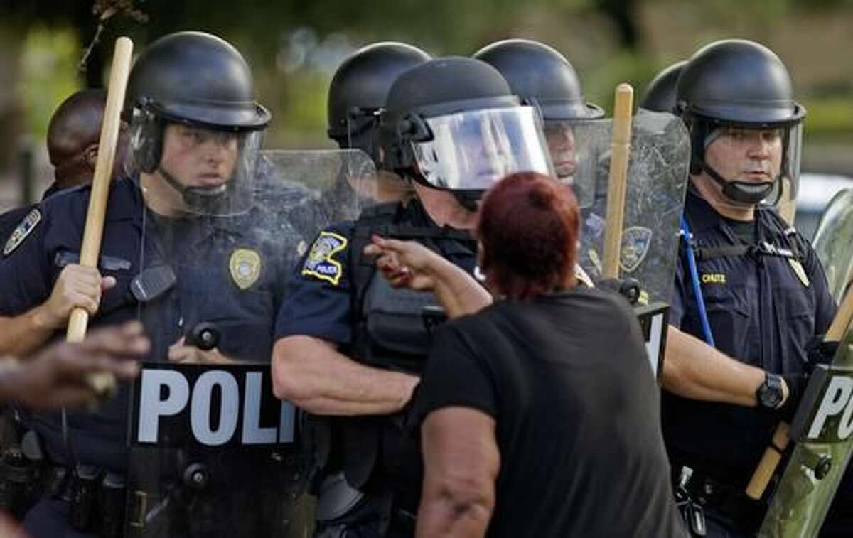 """FILE -In this July 9, 2016 file photo, a protester yells at police in front of the Baton Rouge Police Department headquarters after police arrived in riot gear to clear protesters from the street in Baton Rouge, La. A settlement agreement Tuesday, Nov. 29 resolves a federal lawsuit that accuses law enforcement of trampling on the civil rights of protesters in Baton Rouge following a black man's fatal shooting by police. Plaintiffs' attorneys said their """"memorandum of understanding"""" with state and local police officials affirms that people have the right to peacefully protest. The agreement doesn't include any monetary terms. (AP Photo/Max Becherer, File)"""