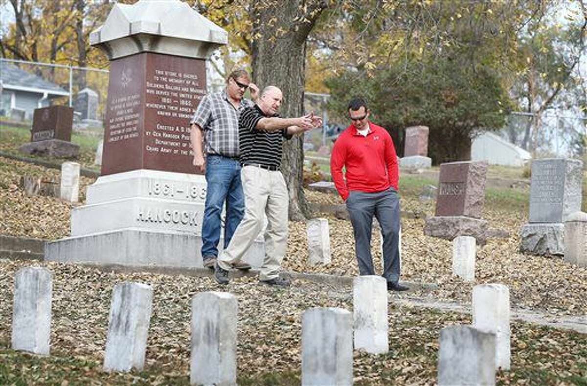 In this photo taken Nov. 2, 2016, Tim Tushla, center, talks to Kelly Bach, left, and Matt Salvatore as they walk through the Grand Army of the Republic section for Civil War veterans at Floyd Cemetery in Sioux City, Iowa. Markers will be added for veterans who do not have any stones on their graves. (Jim Lee/Sioux City Journal via AP)