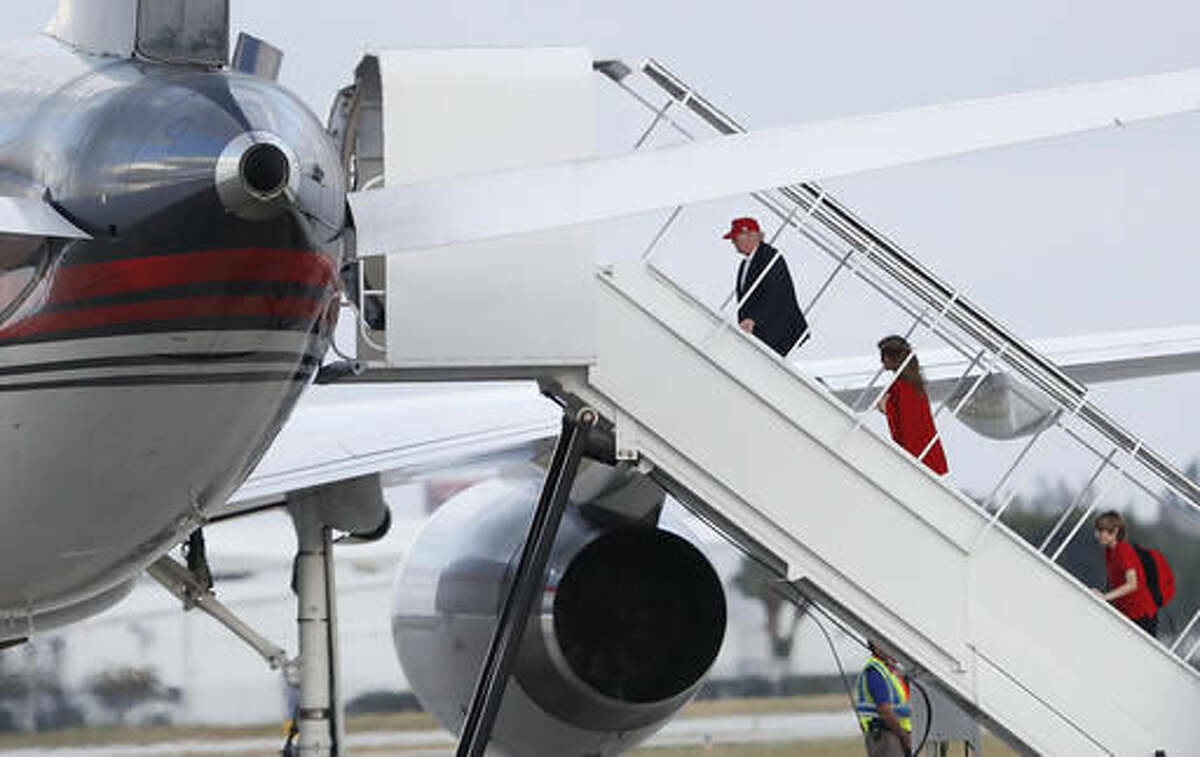President-elect Donald Trump, followed by his wife Melania Trump and son Barron Trump, boards his plane at Palm Beach International Airport, Sunday, Nov. 27, 2016, in West Palm Beach, Fla., en route to New York. (AP Photo/Carolyn Kaster)