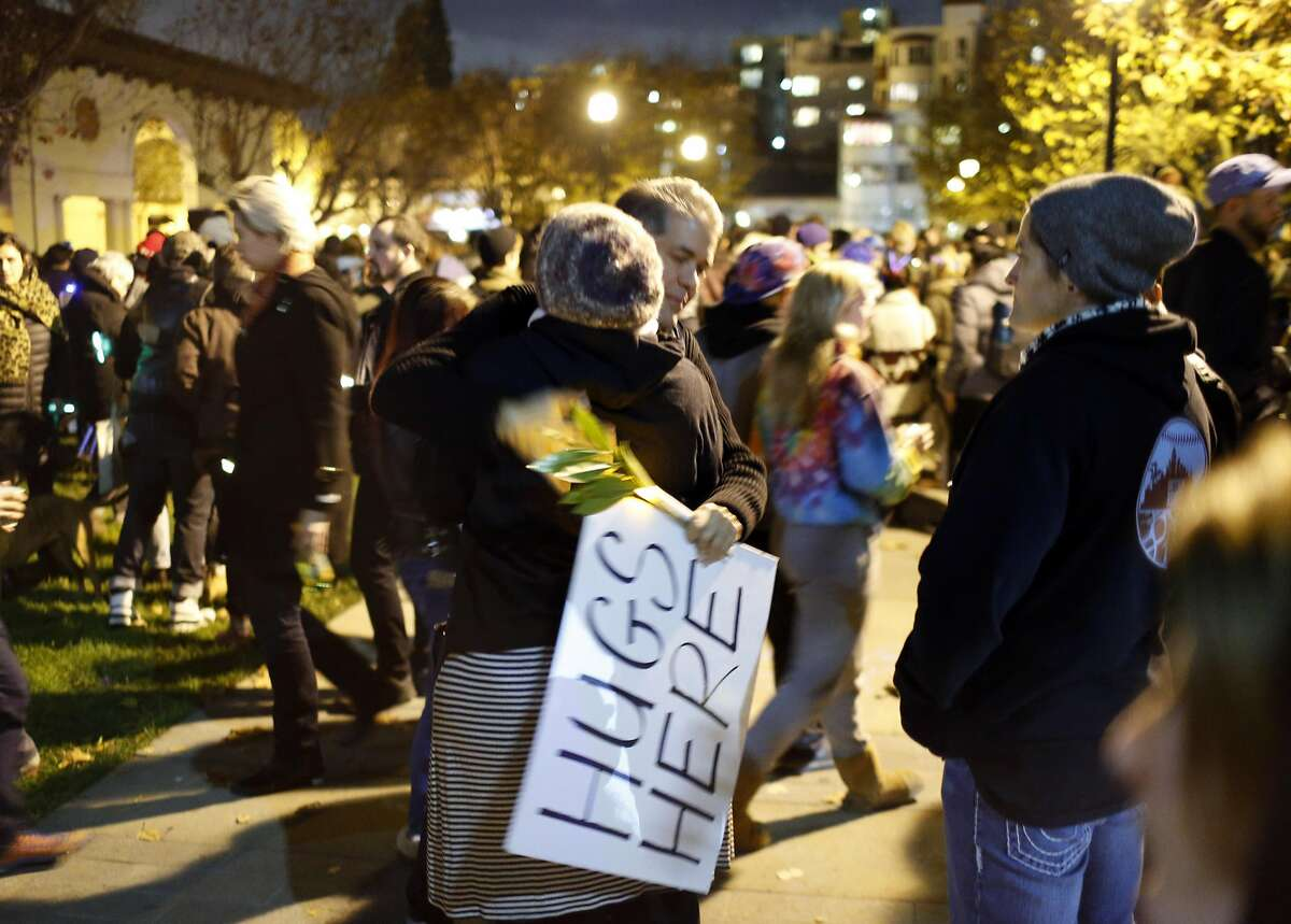 Tex Allen, rear, hugs a woman during a vigil at Lake Merritt as recovery efforts continue following the Ghost Ship fire that has so far claimed 36 lives in Oakland, Calif., on Monday, December 5, 2016.