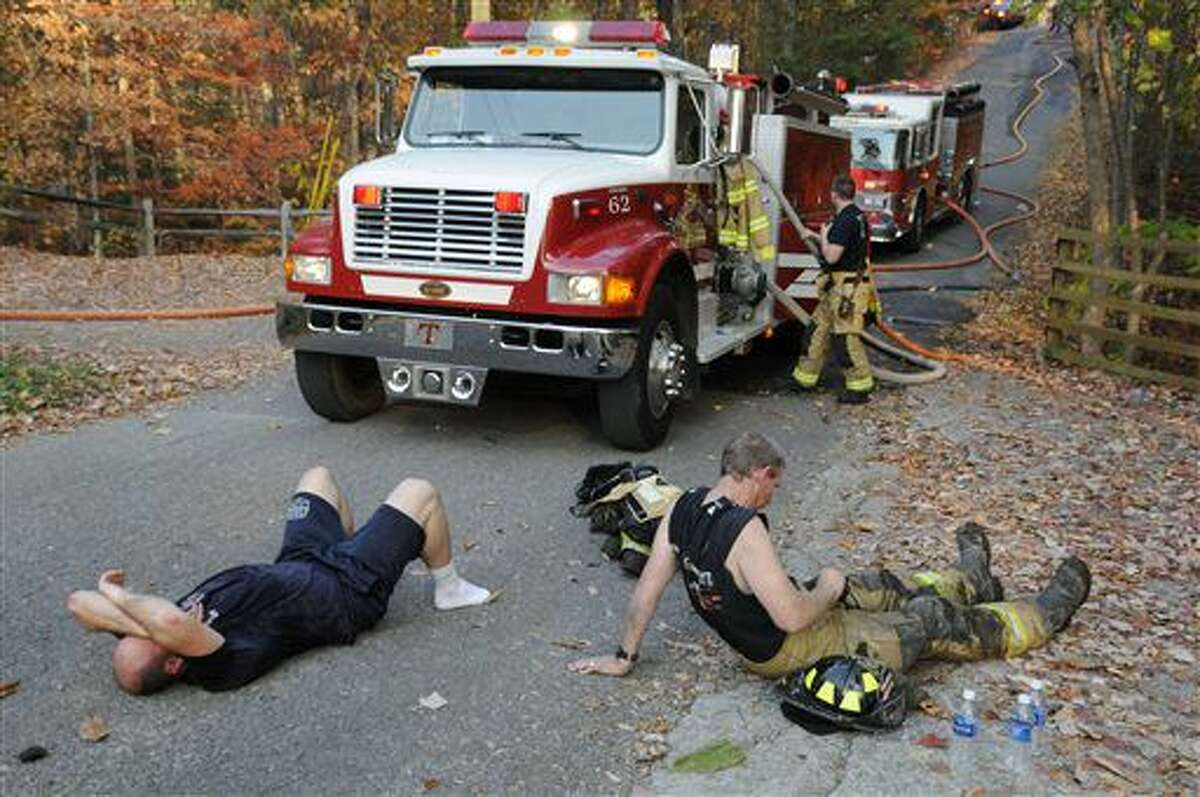 Exhausted firefighters take a break after fighting a cabin and four acre brush fire at a mountain top rental community in Waldens Creek, Tenn., Monday, Nov. 14, 2016. Firefighters from seven departments and Tennessee State Forestry responded to contain the fire. (Curt Habraken/The Mountain Press via AP)