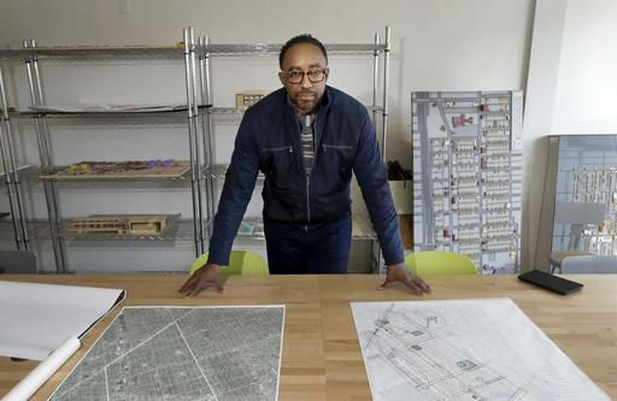 In a Wednesday, Oct. 19, 2016, photo, Hajj Flemings, who won nearly $165,000 from the Knight Foundation Cities Challenge competition a year earlier, poses for a picture at the Detroit Center of Design and Technology in Detroit. Flemings won the grant for his proposal to help small businesses in Detroit develop an online presence and a brand. (AP Photo/Carlos Osorio)