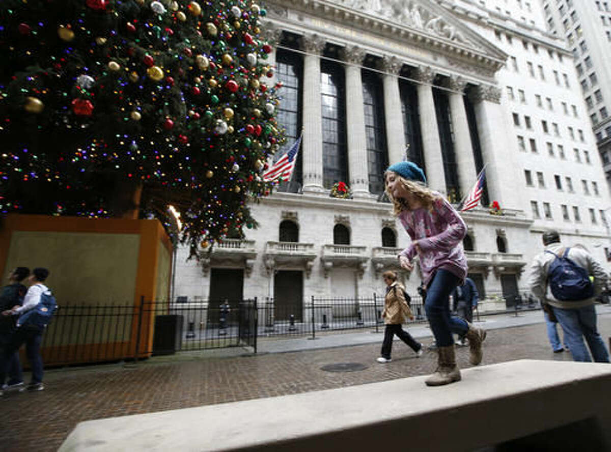 In this photo taken Dec. 24, 2015, a youngster runs along a concrete bench across from the New York Stock Exchange on Christmas Eve, in New York, where warm and balmy temperatures shattered records. A new study says broken daily heat records are going to be far more common than cold ones in the U.S. Normally, the nation should generally have about the same number of hot and cold records. But that's not happening with more than twice as many heat records this decade than cold. (AP Photo/Kathy Willens)