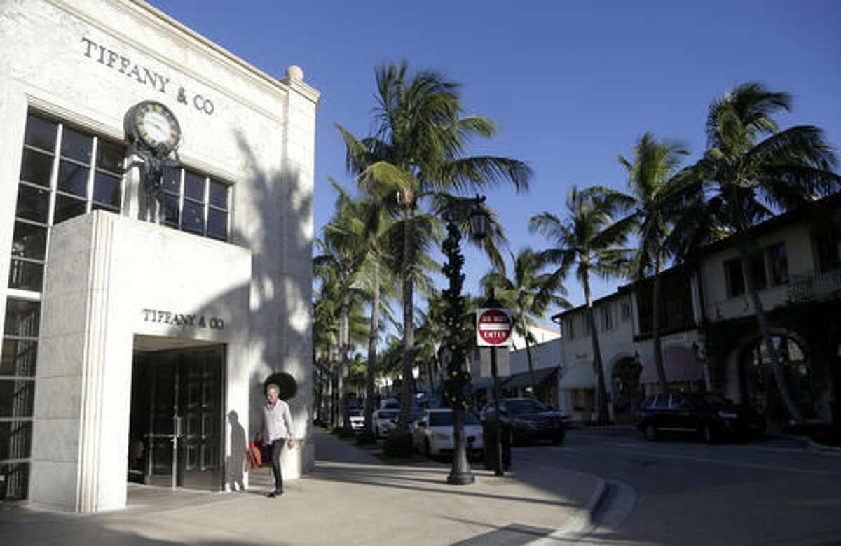 In this Monday, Nov. 21, 2016, photo, a man walks along Worth Avenue; home to upscale shops, boutiques, and restaurants in Palm Beach, Fla. When Trump arrives at his Mar-a-Lago resort for Thanksgiving, it won't be the first time a president-elect has used Palm Beach as his vacation refuge. John Kennedy's family estate, known during his term as the Winter White House, is seven miles north at the other end of Ocean Drive. (AP Photo/Lynne Sladky)