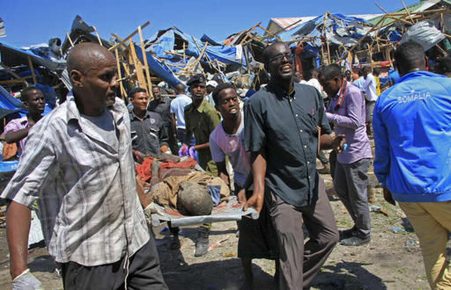 Somali men retrieve the dead body of a person who was killed when a car bomb targeted a police station in the Waberi neighborhood, where President Hassan Sheikh Mohamud was visiting a university, in the capital Mogadishu, Saturday, Nov. 26, 2016. A Somali police official says a car bomb has exploded near a police station in a busy market in the Somali capital, killing a number of people and wounding others. (AP Photo/Farah Abdi Warsameh) Photo: Farah Abdi Warsameh