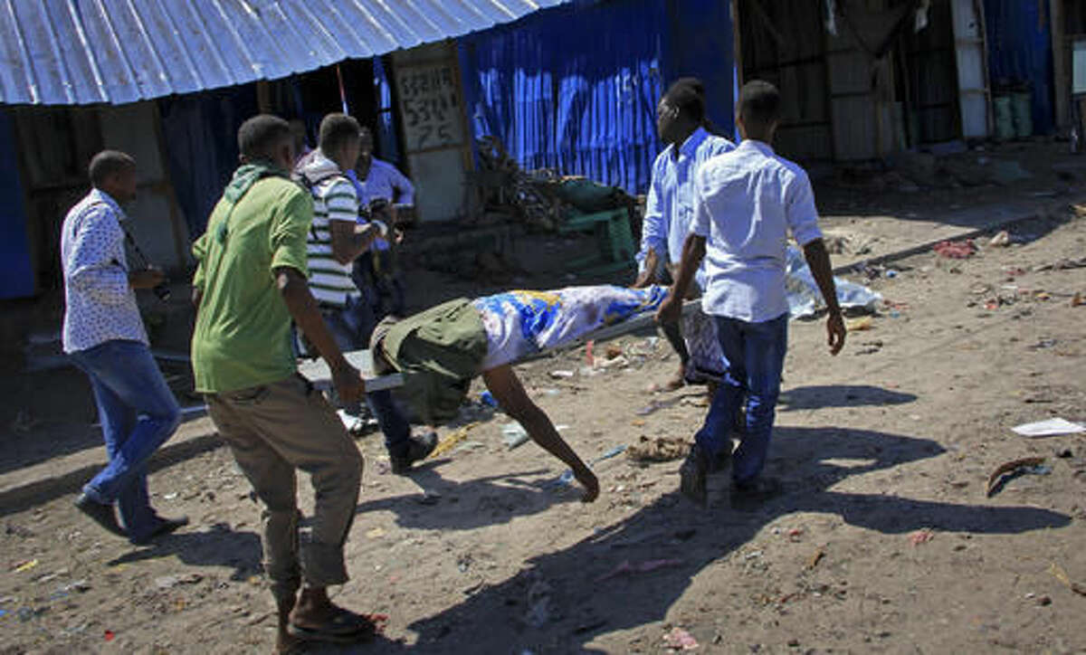 Somali men retrieve the body of a victim killed when a car bomb targeted a police station in the Waberi neighborhood, where President Hassan Sheikh Mohamud was visiting a university, in the capital Mogadishu, Somalia Saturday, Nov. 26, 2016. A Somali police official says a car bomb has exploded near a police station in a busy market in the Somali capital, killing a number of people and wounding others. (AP Photo/Farah Abdi Warsameh)