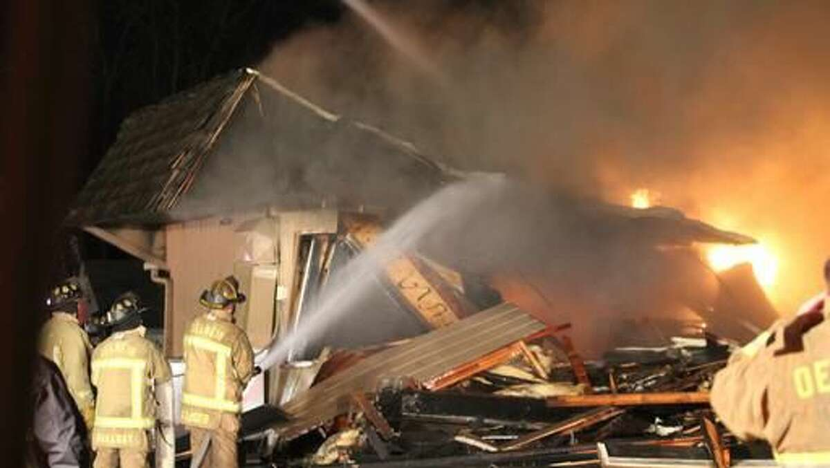 A fire that started in the kitchen of Luigi's destroys the longtime restaurant in Oelwein, Iowa, Saturday, Nov. 12, 2016.. The restaurant's well-known sign in the parking lot was the only thing left standing after Saturday's fire. Firefighters knocked down the walls of the restaurant to extinguish the blaze, so little was left intact. (Jeff Reinitz/