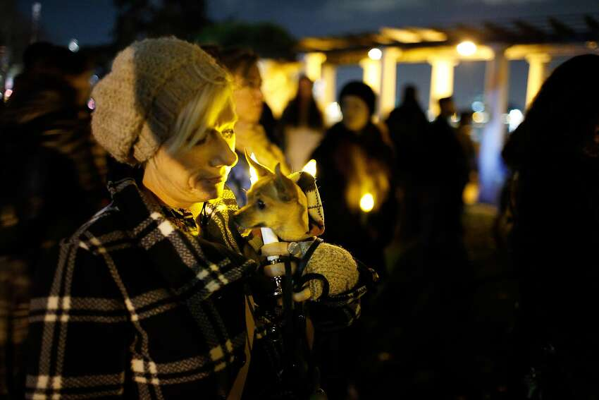 Jaime Tollefson, of Oakland, holds her dog Ruby during a vigil at Lake Merritt as recovery efforts continue following the Ghost Ship fire that has so far claimed 36 lives in Oakland, Calif., on Monday, December 5, 2016.