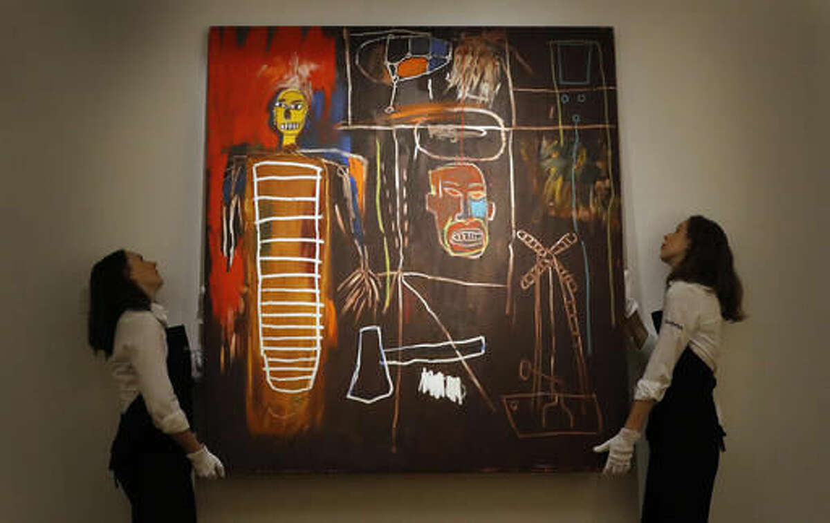 """FILE - This is a Wednesday, July 20, 2016 file photo of Sotheby's employees as they lift the painting """"Air Power"""" by Jean-Michel Basquiat at Sotheby's in London. Buyers have snapped up modern artworks collected by David Bowie at a London auction, with a painting by Jean-Michel Basquiat selling for more than 7 million pounds ($8.8 million). The first part of Sotheby's two-part Bowie sale netted 24.3 million pounds ($30.3 million), more than double its pre-sale estimate. (AP Photo/Frank Augstein, File)"""