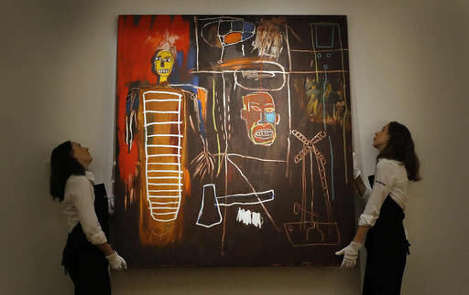 "FILE - This is a Wednesday, July 20, 2016 file photo of Sotheby's employees as they lift the painting ""Air Power"" by Jean-Michel Basquiat at Sotheby's in London. Buyers have snapped up modern artworks collected by David Bowie at a London auction, with a painting by Jean-Michel Basquiat selling for more than 7 million pounds ($8.8 million). The first part of Sotheby's two-part Bowie sale netted 24.3 million pounds ($30.3 million), more than double its pre-sale estimate. (AP Photo/Frank Augstein, File) Photo: Frank Augstein"
