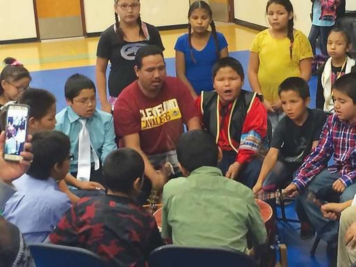 ADVANCE FOR THE WEEKEND OF NOV 18-19 AND THEREAFTER - In a Nov. 2, 2016 photo, Ethan Fightingbear leads a drum group made up of students from Arapaho schools, to celebrate the release of a new application for smart phones and tablets that translates words from English to the Arapaho language. Arapaho elders regularly met to develop the words and translations for the app, ultimately creating 24 categories. (Carl Manning/The Ranger via AP)