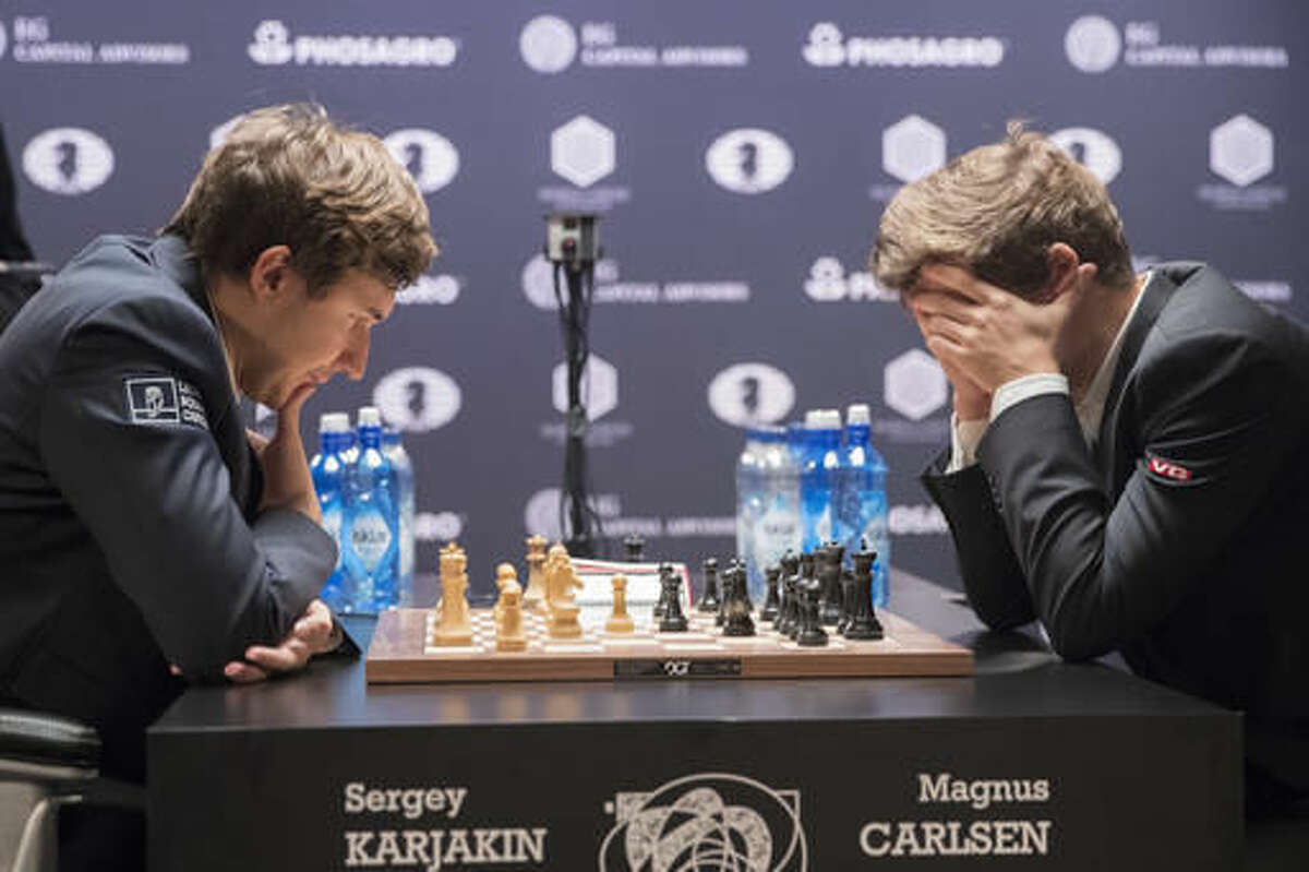 Sergey Karjakin, left, of Russia, and defending champion Magnus Carlsen, of Norway, concentrate on the board during the tie breaker round of the World Chess Championship, Wednesday, Nov. 30, 2016, in New York. (AP Photo/Mary Altaffer)