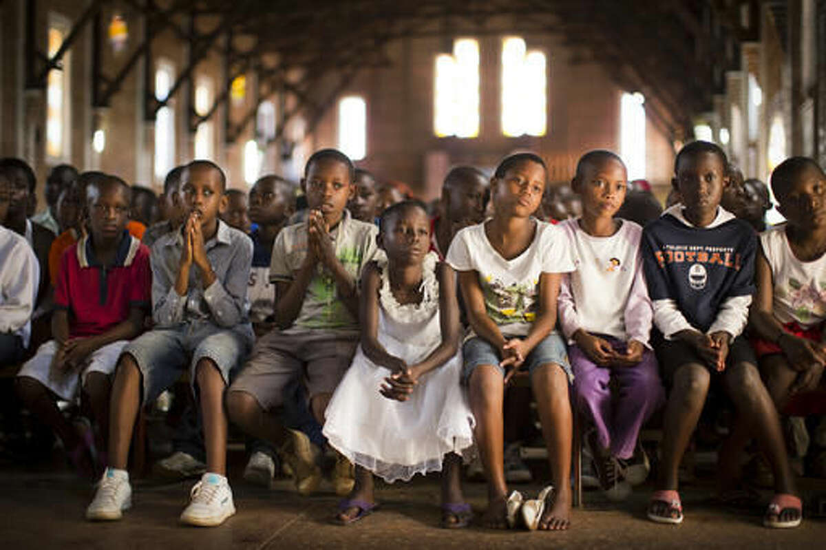 FILE - In this Sunday, April 6, 2014 file photo, Rwandan children listen and pray during a Sunday morning service at the Saint-Famille Catholic church, the scene of many killings during the 1994 genocide, in the capital Kigali, Rwanda. The Catholic Church in Rwanda apologized on Sunday, Nov. 20, 2016, for the church's role in the 1994 genocide, saying it regretted the actions of those who participated in the massacres. (AP Photo/Ben Curtis, File)