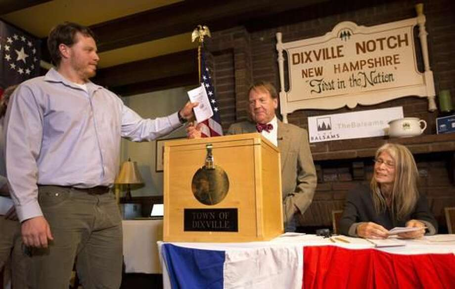 CORRECTS TO DIXVILLE NOTCH FROM DIXVILLE NOTCHE AND CLARIFIES VOTES- Dixville Notch's first voter Clay Smith drops his ballot into the box as moderator Tom Tillotson watches Tuesday, Nov. 8, 2016, in Dixville Notch, N.H. Dixville Notch, where the nation's first voters cast their ballots on Election Day, had Democratic presidential candidate Hillary Clinton beating Republican Donald Trump. (AP Photo/Jim Cole) Photo: Jim Cole