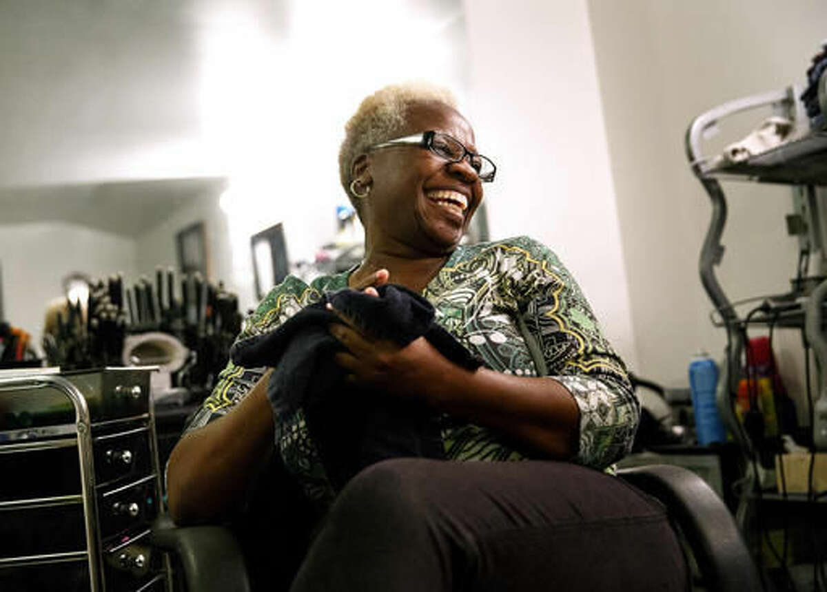 In this Oct. 20, 2016 photo, Marcella Kincaid who was convicted of a felony in 1991, smiles in her hair salon in Springfield, Ill. Kincaid was convicted of selling cocaine, but was granted clemency recently by Gov. Bruce Rauner and her record could soon be cleared. Now a substance abuse counselor for the Family Guidance Center, Kincaid said getting her record expunged paves the way for her pursuing her dream of opening up multiple sober living homes in Springfield. (Rich Saal/The State Journal-Register via AP)