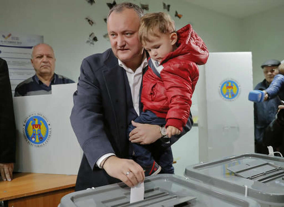 Socialists Party presidential candidate Igor Dodon holds his son Nikolai as he casts his ballot in Chisinau, Moldova, Sunday, Nov. 13, 2016. Moldovans are voting in a presidential election Sunday in which the favorite Dodon has promised to restore ties with Russia that cooled after the former Soviet republic signed a trade deal with the European Union. (AP Photo/Vadim Ghirda)