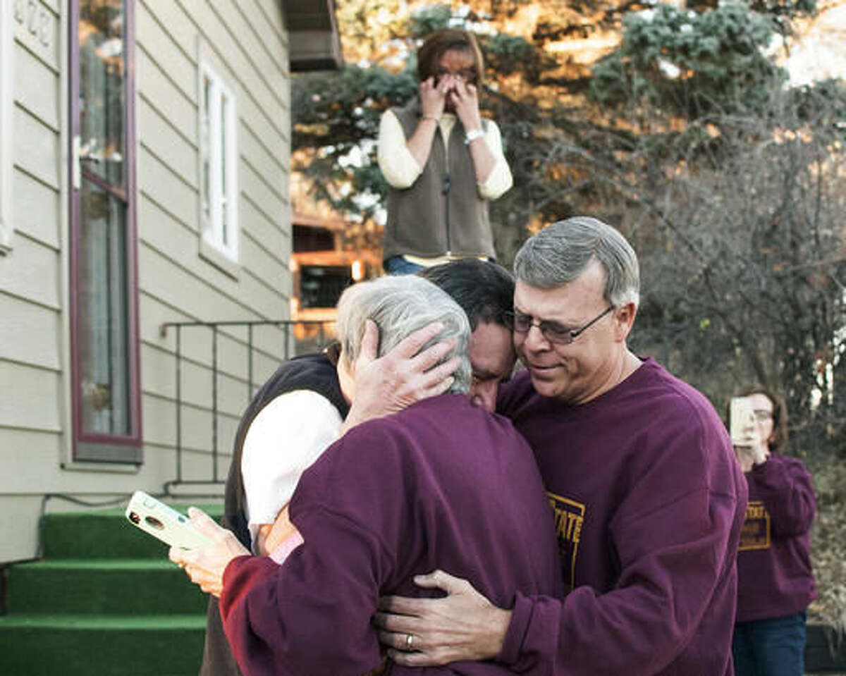 In this Nov. 11, 2016, photo, Mike Jennings, back, hugs his sister Sandy Erby and brother Jim Reimer at Jennings' home in Havre, Mont. The three siblings, the last survivors of seven who were given up for adoption, met for the first time. (Teresa Getten/Havre Daily News via AP)