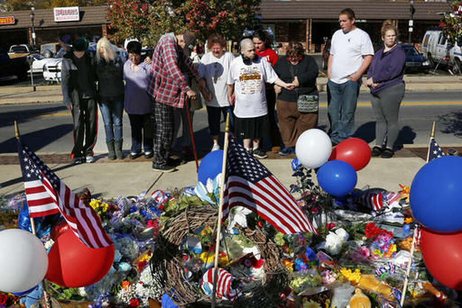 A group prays in front of a makeshift memorial for the Canonsburg Police officers who were shot when they responded to a domestic call early Thursday, Nov 10, 2016, in Canonsburg, Pa. A gunman with a history of domestic abuse shot at police officers before he and a woman were found dead following a reported fight at their apartment, authorities said. (AP Photo/Gene J. Puskar) Photo: Gene J. Puskar