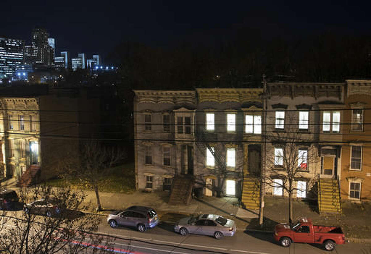 In this Monday, Nov. 14, 2016 photo, windows in vacant houses are illuminated with LED lights in Albany, N.Y. Windows in more than 150 abandoned buildings in three upstate New York cities have been fitted with light-emitting diodes that steadily brighten and fade, giving the effect of slow breathing. The two-month public art project provides something pretty for gritty neighborhoods of Albany, Schenectady and Troy. (AP Photo/Mike Groll)