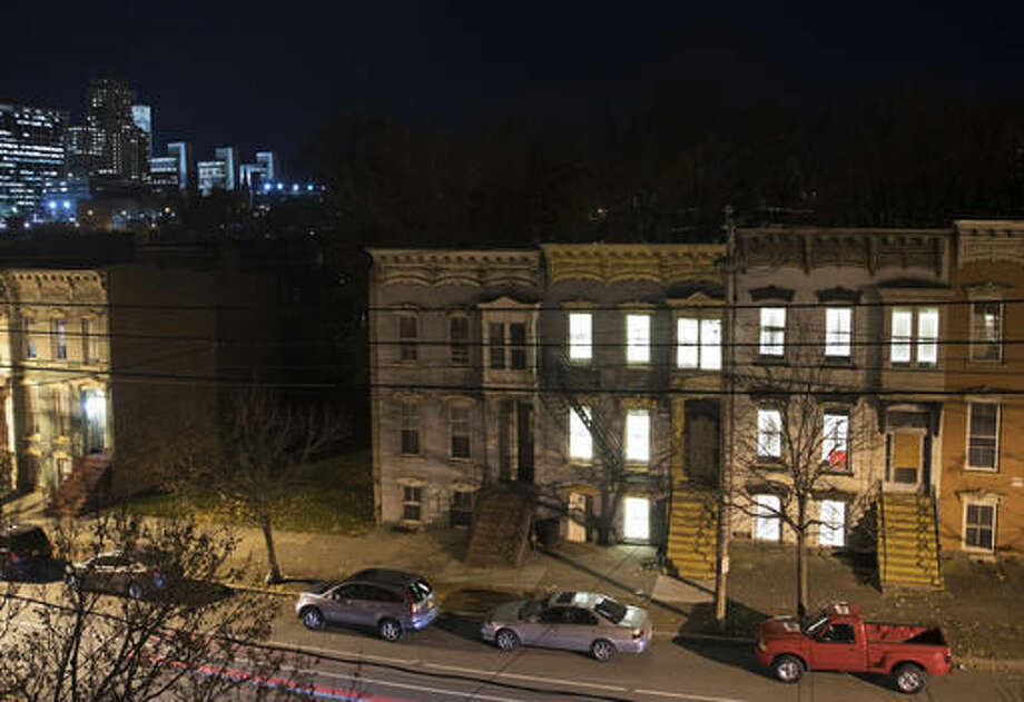 In this Monday, Nov. 14, 2016 photo, windows in vacant houses are illuminated with LED lights in Albany, N.Y. Windows in more than 150 abandoned buildings in three upstate New York cities have been fitted with light-emitting diodes that steadily brighten and fade, giving the effect of slow breathing. The two-month public art project provides something pretty for gritty neighborhoods of Albany, Schenectady and Troy. (AP Photo/Mike Groll) Photo: Mike Groll