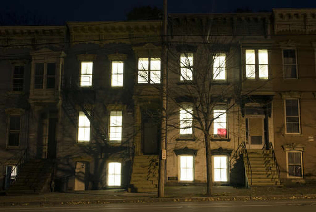 In this Friday, Oct. 28, 2016 photo, windows in vacant buildings are illuminated with LED lights in Albany, N.Y. Windows in more than 150 abandoned buildings in three upstate New York cities have been fitted with light-emitting diodes that steadily brighten and fade, giving the effect of slow breathing. The two-month public art project provides something pretty for gritty neighborhoods of Albany, Schenectady and Troy. (AP Photo/Mike Groll)