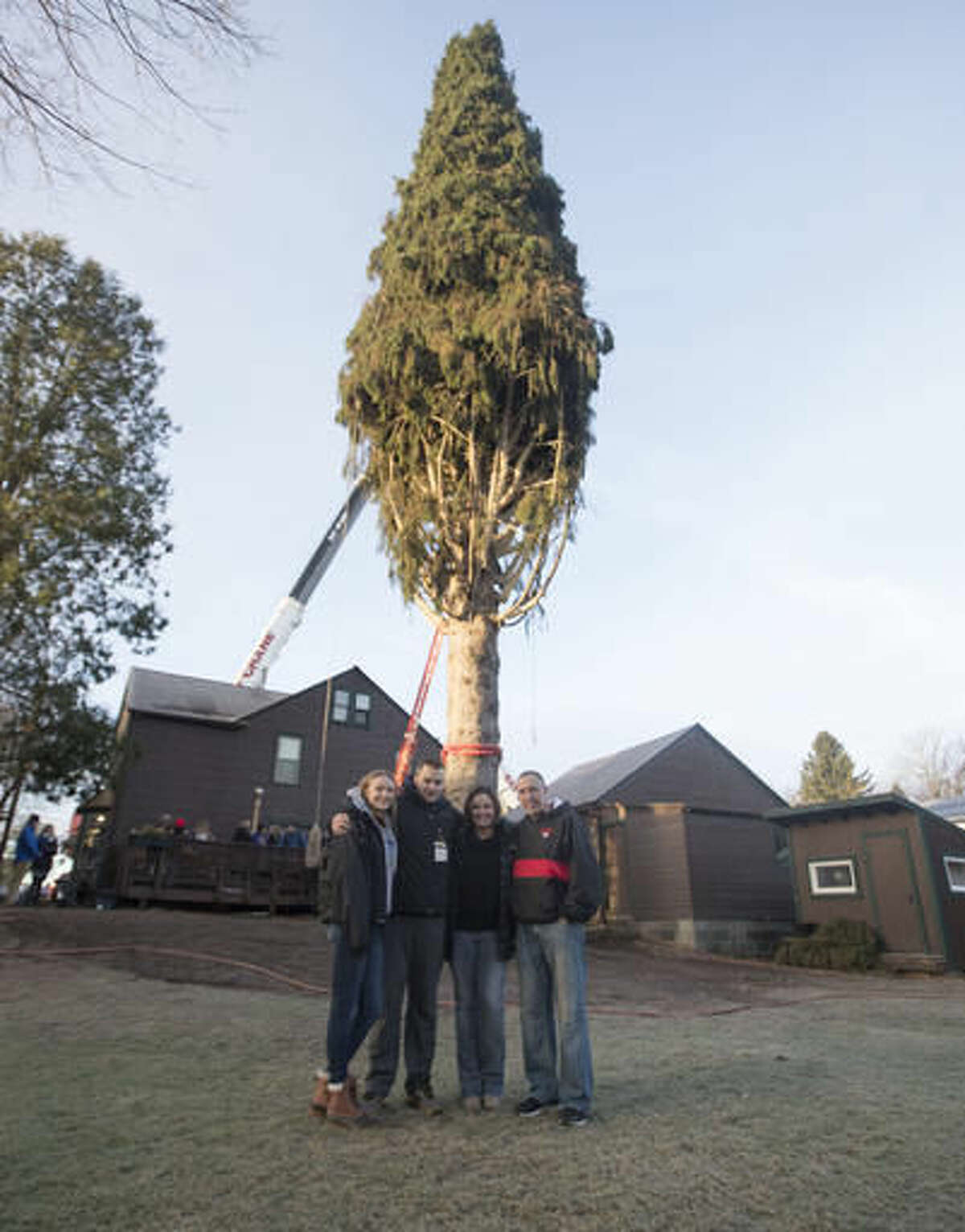 Graig Eichler, right, his wife Angie and their children Ava and Brock pose in front of a 94-foot Norway spruce that will serve as the Christmas tree at Rockefeller Center on Thursday, Nov. 10, 2016, in Oneonta, N.Y. The spruce is due to arrive Saturday in Manhattan, about 140 miles away. (AP Photo/Mike Groll)
