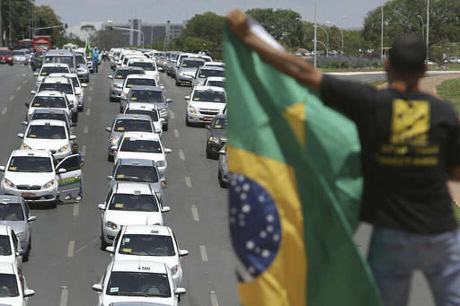 Taxi drivers protest against the online transportation service Uber, in Brasilia, Brazil, Tuesday, Nov. 8, 2016. More than one thousand taxi drivers, many in their vehicles, staged a protest in front of Congress demanding that it prohibits the U.S. based company from operating in Latin America's largest nation. (AP Photo/Eraldo Peres) Photo: Eraldo Peres