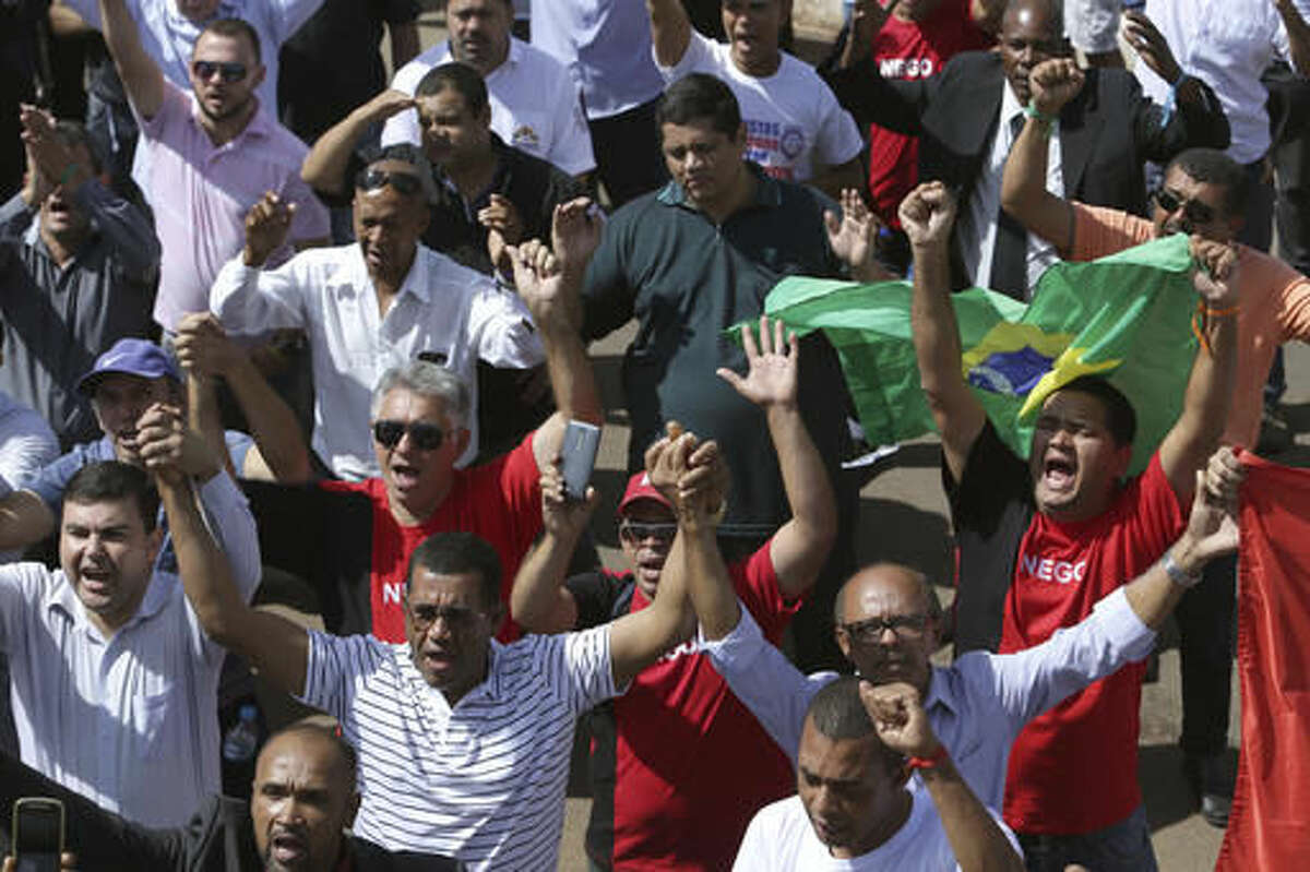 Taxi drivers protest against the online transportation service Uber, in Brasilia, Brazil, Tuesday, Nov. 8, 2016. More than one thousand taxi drivers, many in their vehicles, staged a protest in front of Congress demanding that it prohibits the U.S. based company from operating in Latin America's largest nation. (AP Photo/Eraldo Peres)