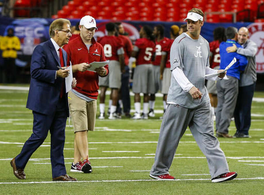 Alabama head coach Nick Saban, left, talks with Alabama offensive coordinator Lane Kiffin, right, during practice for the Southeastern Conference Championship NCAA college football game where they will play Florida, Friday, Dec. 2, 2016, in Atlanta. (AP Photo/Butch Dill)