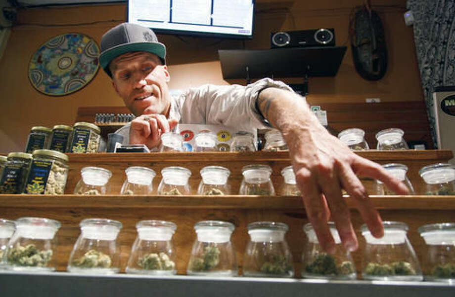 FILE- - In this Sept. 28, 2015, file photo, Shane Cavanaugh, owner of Amazon Organics, a pot dispensary in Eugene, Ore., arranges the cannabis display in his store. The government still has many means to slow or stop the marijuana train and President-elect Donald Trump's nomination of Alabama Sen. Jeff Sessions to be the next attorney general has raised fears that the new administration could crack down on weed-tolerant states. (AP Photo/Ryan Kang, File) Photo: Ryan Kang
