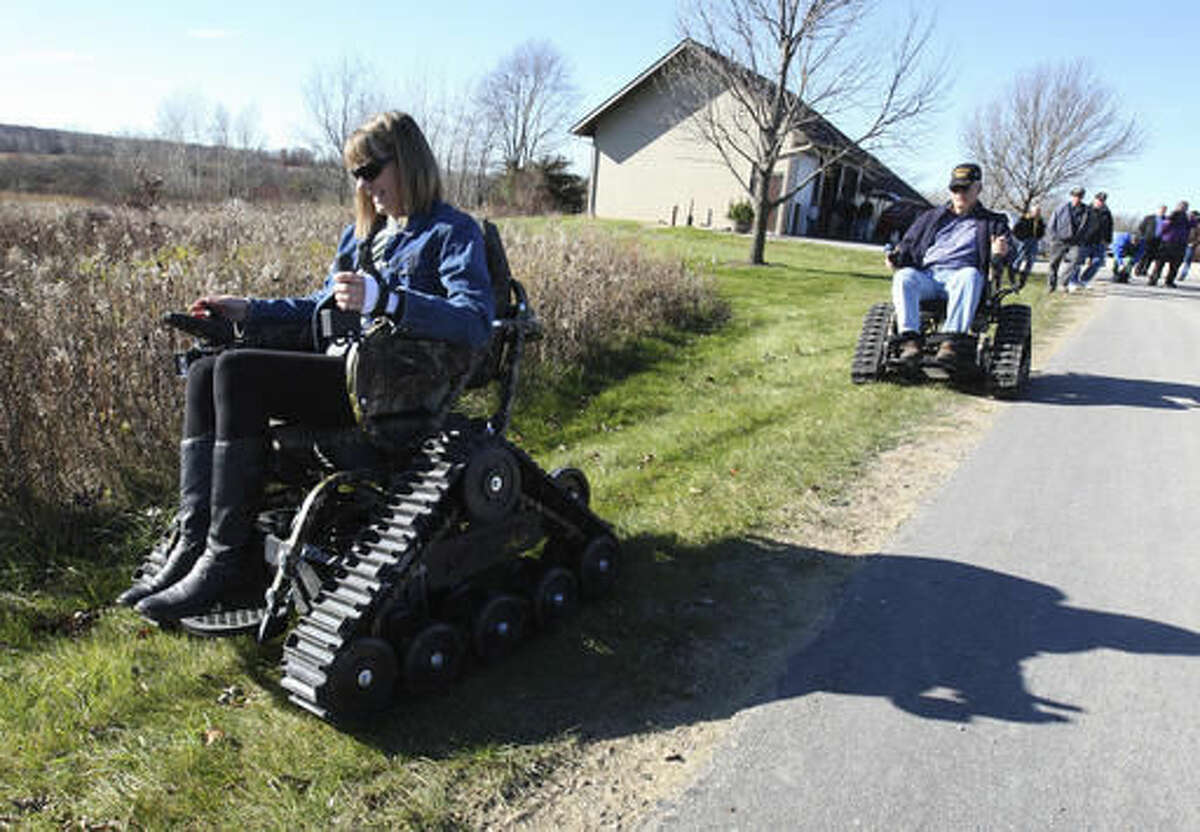 ADVANCE FOR WEEKEND EDITIONS, NOV. 12-13 - In this Wednesday, Nov. 9, 2016 photo, Gold Star parent Kay Swenson, VFW commander Gary Pike, and others try out four Action Trak wheelchairs, at an event at Chester Woods county park near Rochester, MN. The chairs will be used for disabled veterans to get out and hunt and enjoy the outdoors. (Ken Klotzbach /The Rochester Post-Bulletin via AP)